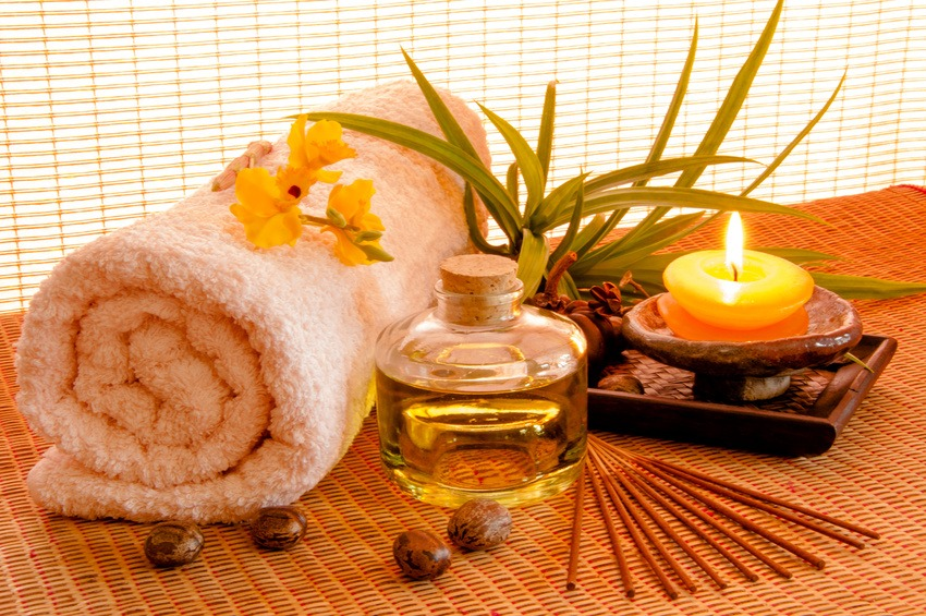 Essential oil bottles, towels, candle and flower in health spa for spa treatment.
